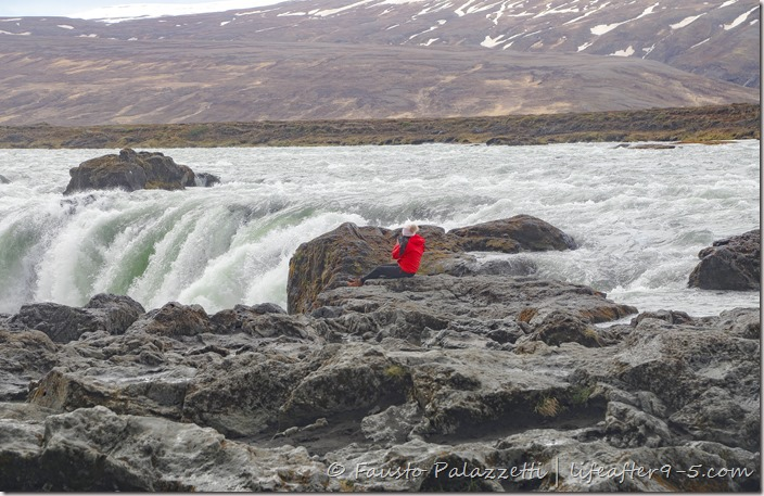 Women in red jacket sitting at the edge of Góðafoss