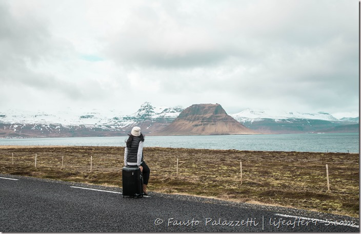 Woman sitting on luggage looking at the stunning view of Snæfellsnes Peninsula