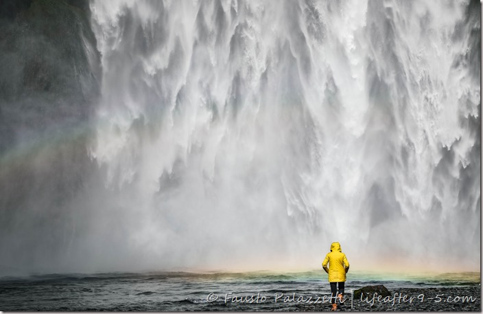 Women in yellow rain coat standing in front of Skogafoss