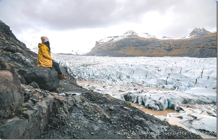 Women sitting by side of cliff enjoying the view of Svínafellsjökull Glacier Tongue