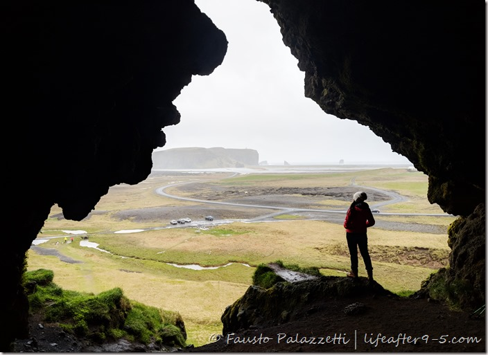 Woman standing in Loftsalahellir Cave with views of Dyrhólaey Archway