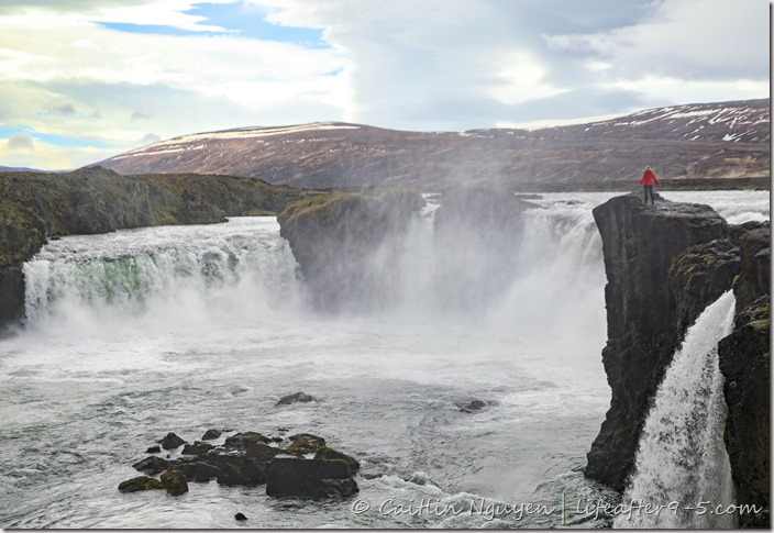 Woman in red jacket standing at the edge overlooking Godafoss