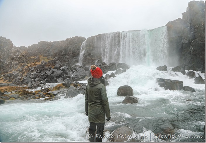 Woman standing in front of Öxarárfoss in Thingvellir