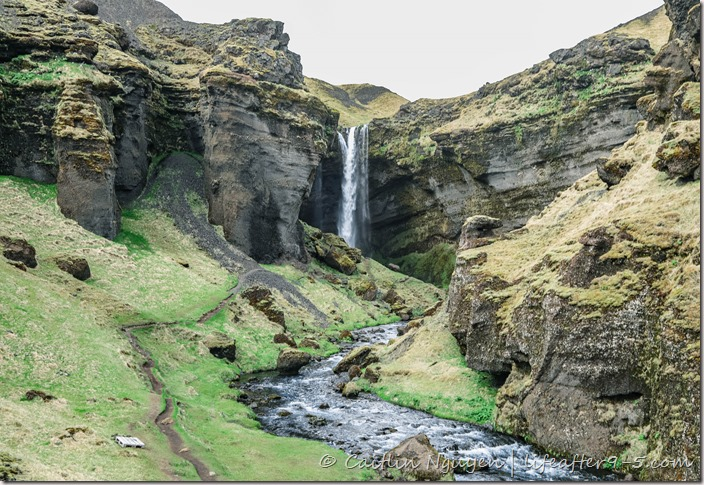 Hidden waterfall Kvernufoss surrounded by lush landscape