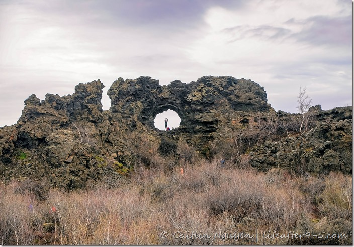 People posing in rock formation at Dimmuborgir