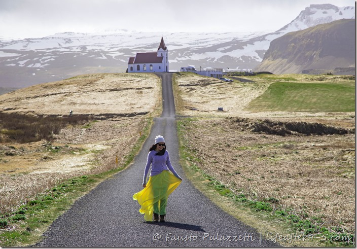 Woman on empty street in Ingjaldshóll with church and mountain background