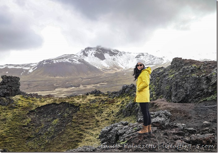 Woman in yellow jacket at the top of Saxhóll crater with mountain in background