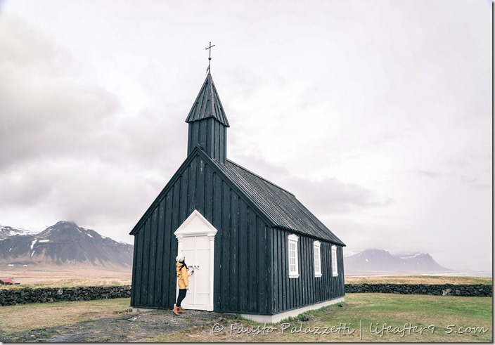 Woman standing in front of Black Church in Iceland