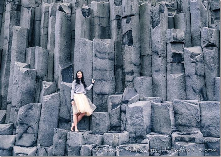 Woman standing on basalt columns at Reynisfjara black beach