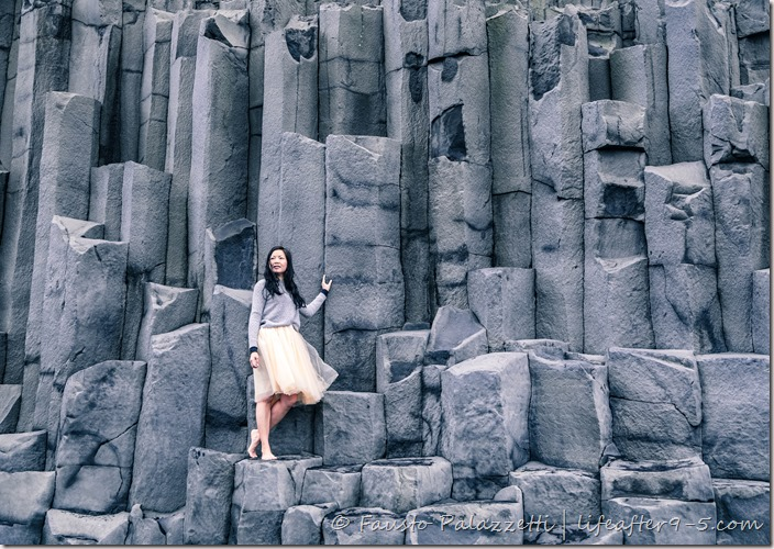 Woman standing on basalt columns at Reynisfjara black beach