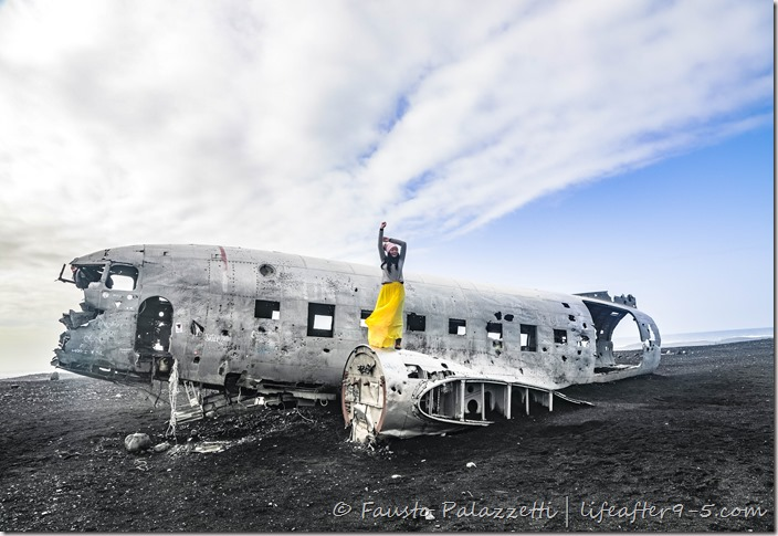 Woman posing on top of Sólheimasandur plane wreck
