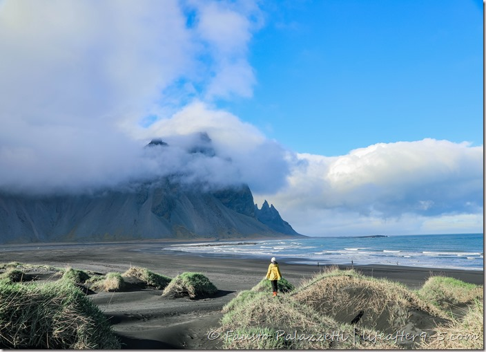 Woman standing on the grassy hills at Stokksnes black beach