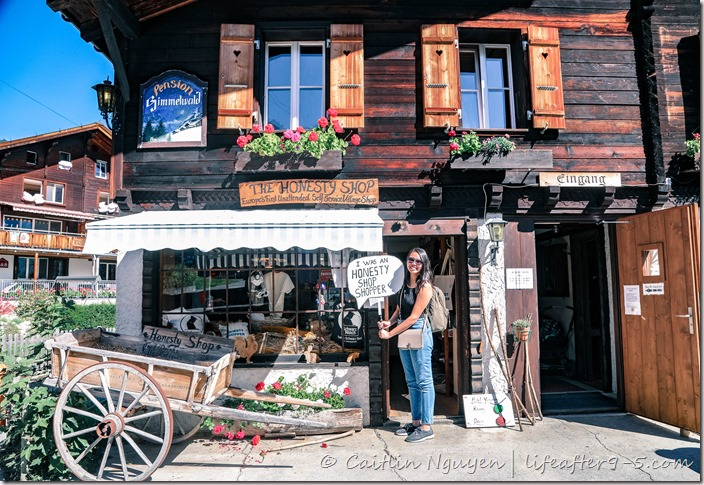 Woman standing in front of honesty shop in Gimmelwald